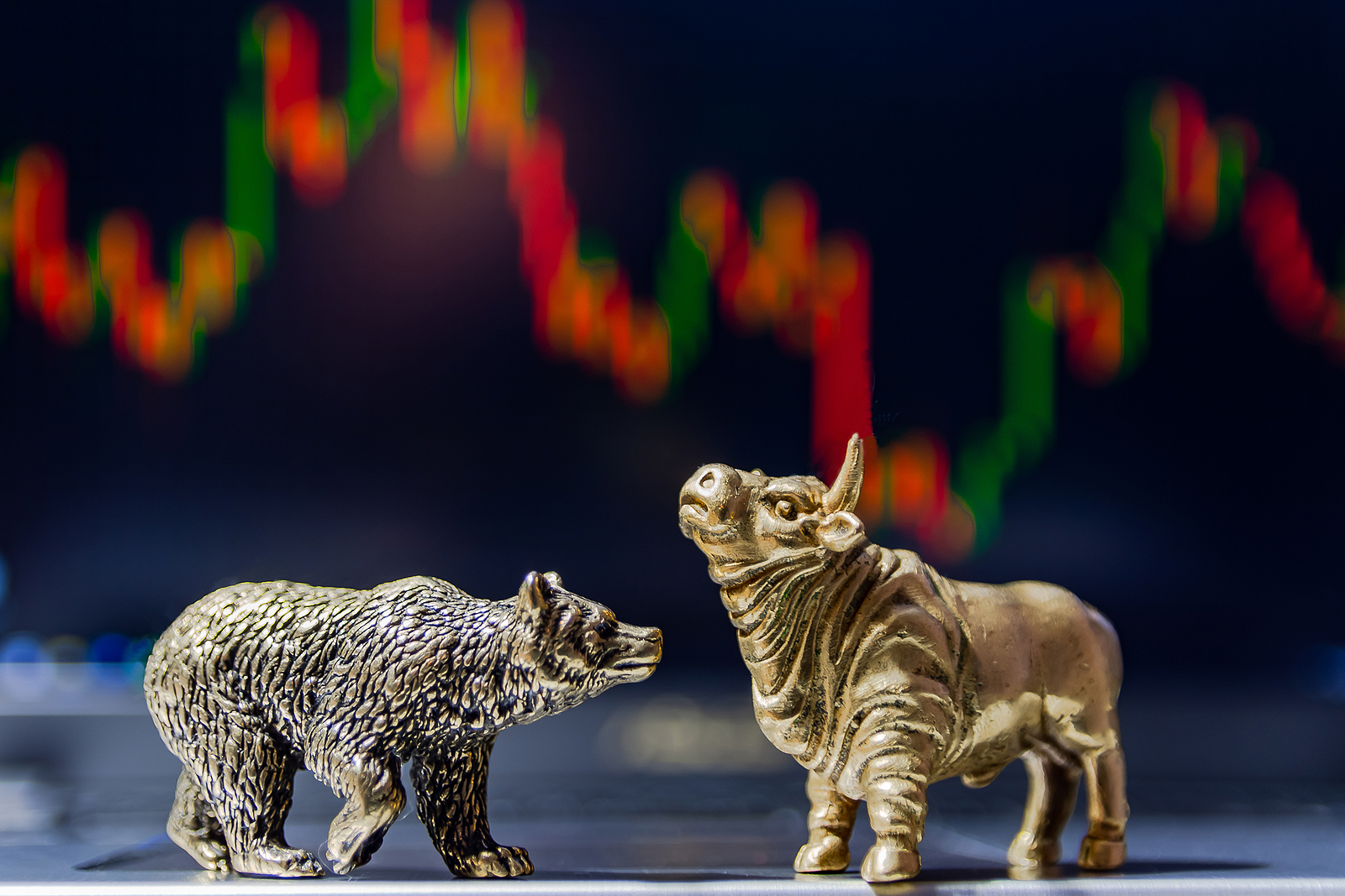 Golden bear and bull in front of stock price chart