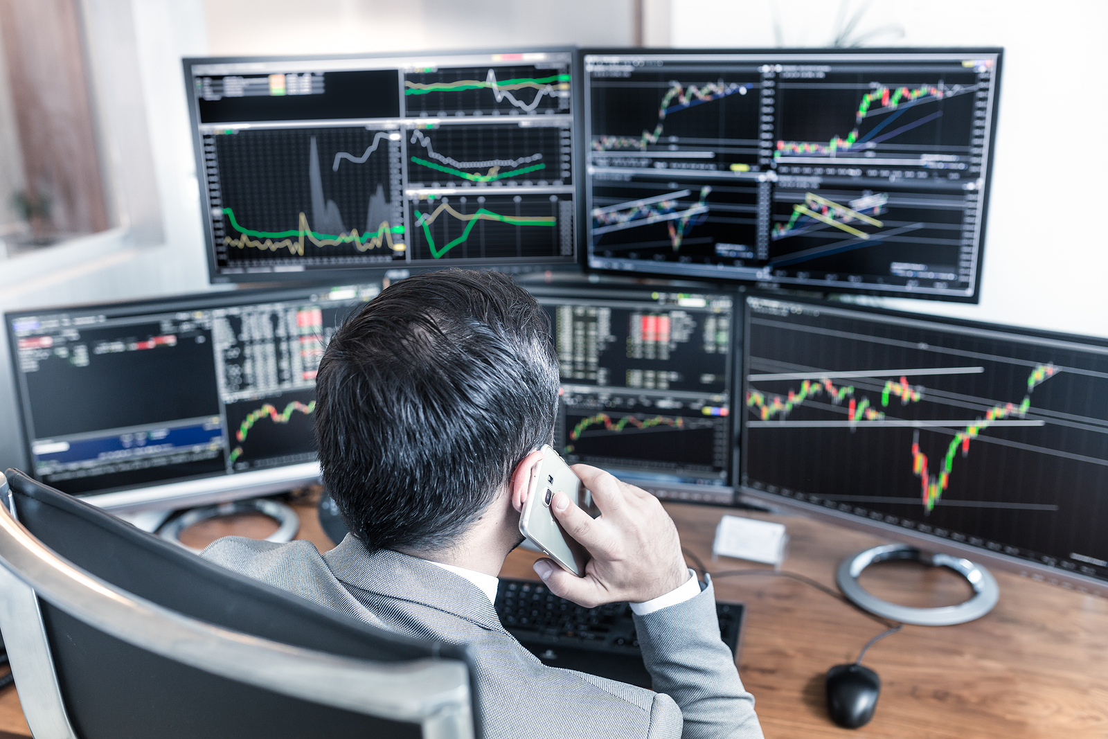 Trader in front of five trading screens