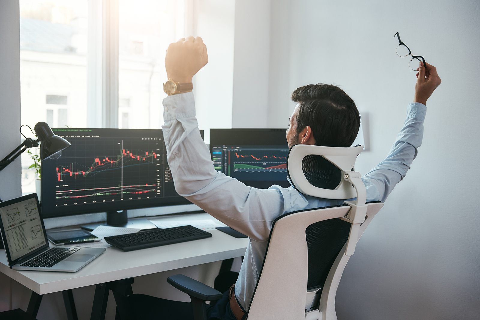 Trader celebrating in front of trading screens